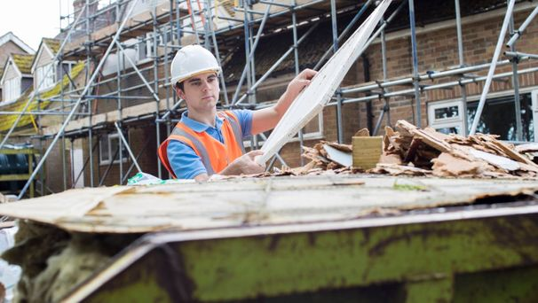 A builder putting recyclable materials in to a skip